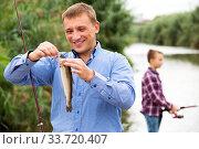Man standing on lake shore with hook fish. Стоковое фото, фотограф Яков Филимонов / Фотобанк Лори