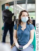 Купить «Woman in mask with earphones riding tram», фото № 33720475, снято 26 мая 2020 г. (c) Яков Филимонов / Фотобанк Лори