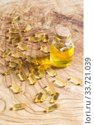 Купить «Флакон с растительным маслом и желатиновые капсулы с рыбьим жиром в солнечных лучах на деревянной подставке. Омега-3  незаменимые полиненасыщенные жирные кислоты», фото № 33721039, снято 5 мая 2020 г. (c) Наталья Гармашева / Фотобанк Лори