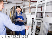 Купить «Production worker in coverall demonstrating different PVC windows to customer», фото № 33721355, снято 30 марта 2017 г. (c) Яков Филимонов / Фотобанк Лори