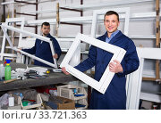 Купить «Production workers in coverall with different finished PVC profiles and windows at factory», фото № 33721363, снято 30 марта 2017 г. (c) Яков Филимонов / Фотобанк Лори