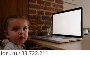Cute toddler sitting near table and watching video on modern laptop with blank screen at home. Стоковое видео, видеограф Ekaterina Demidova / Фотобанк Лори