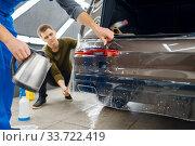 Купить «Specialists applies car protection film on bumper», фото № 33722419, снято 20 марта 2020 г. (c) Tryapitsyn Sergiy / Фотобанк Лори