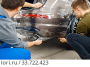 Купить «Two workers applies car protection film on bumper», фото № 33722423, снято 20 марта 2020 г. (c) Tryapitsyn Sergiy / Фотобанк Лори