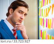 Купить «Young handsome employee with many conflicting priorities», фото № 33723927, снято 15 августа 2018 г. (c) Elnur / Фотобанк Лори