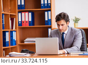Купить «Young employee working in the office», фото № 33724115, снято 9 августа 2018 г. (c) Elnur / Фотобанк Лори