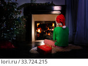 Boy wait with present for Christmas near fireplace. Стоковое фото, фотограф Сергей Новиков / Фотобанк Лори