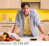 Купить «Young man calculating expences for vegetables in kitchen», фото № 33724267, снято 3 августа 2018 г. (c) Elnur / Фотобанк Лори
