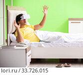 Купить «Young man with virtual glasses in the bedroom», фото № 33726015, снято 22 июня 2018 г. (c) Elnur / Фотобанк Лори