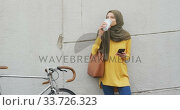 Woman wearing hijab drinking in the street with a take away coffee . Стоковое видео, агентство Wavebreak Media / Фотобанк Лори