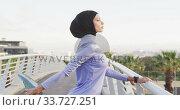 Купить «Side view of woman wearing hijab stretching outside looking at camera», видеоролик № 33727251, снято 14 февраля 2020 г. (c) Wavebreak Media / Фотобанк Лори
