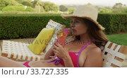Купить «Caucasian woman drinking cocktail near the pool during a sunny day», видеоролик № 33727335, снято 28 ноября 2019 г. (c) Wavebreak Media / Фотобанк Лори