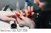 Купить «Doing manicure in the beauty salon - applying base on the nail», видеоролик № 33727755, снято 3 июля 2020 г. (c) Константин Шишкин / Фотобанк Лори