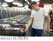 Man passing baffle gate in metro station. Стоковое фото, фотограф Яков Филимонов / Фотобанк Лори