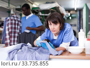 Купить «Woman working in dry cleaner», фото № 33735855, снято 15 января 2019 г. (c) Яков Филимонов / Фотобанк Лори