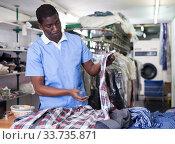 Man inspecting clothing after dry cleaning. Стоковое фото, фотограф Яков Филимонов / Фотобанк Лори