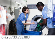 Купить «Laundry workers putting clothes in washing machine», фото № 33735883, снято 15 января 2019 г. (c) Яков Филимонов / Фотобанк Лори