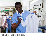 Купить «Man worker checking quality of cleaning clothes», фото № 33735887, снято 15 января 2019 г. (c) Яков Филимонов / Фотобанк Лори