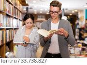 Joyful handsome man and girl choosing books. Стоковое фото, фотограф Яков Филимонов / Фотобанк Лори