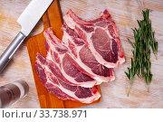 Купить «Raw pork's chops and rosemary on wooden surface», фото № 33738971, снято 30 мая 2020 г. (c) Яков Филимонов / Фотобанк Лори