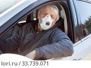 Купить «Retirement age man driving a car wearing dust face mask, driver sitting inside a vehicle», фото № 33739071, снято 10 мая 2020 г. (c) Кекяляйнен Андрей / Фотобанк Лори