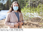 Купить «Attractive young woman wearing beige coat and medical mask standing in spring forest, portrait with copyspace», фото № 33739075, снято 7 мая 2020 г. (c) Кекяляйнен Андрей / Фотобанк Лори