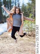 Happy woman hopping in the park and celebrating. Caucasian female wearing beige coat. Стоковое фото, фотограф Кекяляйнен Андрей / Фотобанк Лори