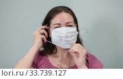 Женщина надевает медицинскую маску на лицо. Стоковое видео, видеограф Кекяляйнен Андрей / Фотобанк Лори