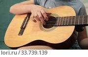 Купить «Children hand pluck the strings and fretboard of a yellow acoustic guitar, close up view», видеоролик № 33739139, снято 2 марта 2020 г. (c) Кекяляйнен Андрей / Фотобанк Лори
