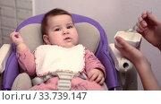 Первый прикорм маленького ребенка. Стоковое видео, видеограф Кекяляйнен Андрей / Фотобанк Лори