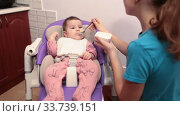 Купить «Teenage girl feeding her sister with teaspoon with additional food, first eating with complementary foods», видеоролик № 33739151, снято 3 февраля 2020 г. (c) Кекяляйнен Андрей / Фотобанк Лори