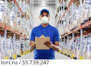 Купить «delivery man in mask or respirator at warehouse», фото № 33739247, снято 12 января 2019 г. (c) Syda Productions / Фотобанк Лори