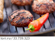 burger meat cutlets and pepper roasting on grill. Стоковое фото, фотограф Syda Productions / Фотобанк Лори