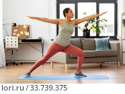 Купить «african woman doing yoga warrior pose at home», фото № 33739375, снято 25 марта 2020 г. (c) Syda Productions / Фотобанк Лори