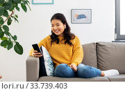 Купить «asian woman with earphones and smartphone at home», фото № 33739403, снято 14 марта 2020 г. (c) Syda Productions / Фотобанк Лори