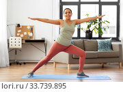 Купить «african woman doing yoga warrior pose at home», фото № 33739895, снято 25 марта 2020 г. (c) Syda Productions / Фотобанк Лори