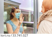 ill woman in mask looking at friend through window. Стоковое фото, фотограф Syda Productions / Фотобанк Лори