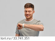 smiling young man looking at smart watch. Стоковое фото, фотограф Syda Productions / Фотобанк Лори