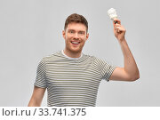 Купить «smiling young man holding lighting bulb», фото № 33741375, снято 21 марта 2020 г. (c) Syda Productions / Фотобанк Лори