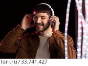 Купить «man in headphones over neon lights of night club», фото № 33741427, снято 22 февраля 2020 г. (c) Syda Productions / Фотобанк Лори