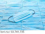 Купить «Medical mask on the same blue background from protective masks. Top view.», фото № 33741735, снято 2 мая 2020 г. (c) Ярослав Данильченко / Фотобанк Лори