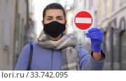 Купить «woman in face mask with stop sign in city», видеоролик № 33742095, снято 12 апреля 2020 г. (c) Syda Productions / Фотобанк Лори
