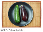 Purple eggplant and pale green zucchini squash on a gray plate on a cane tablecloth. Стоковое фото, фотограф Евгений Харитонов / Фотобанк Лори