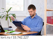 Купить «Деловой человек читает в папке распечатанный отчет», фото № 33742227, снято 3 мая 2020 г. (c) Иванов Алексей / Фотобанк Лори