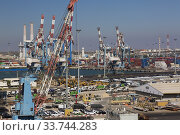 Купить «Four-link cargo loading crane on dock with parked motor vehicles ready for shipping plus container loading cranes in background, Ashdod Port, Israel.», фото № 33744283, снято 4 октября 2019 г. (c) age Fotostock / Фотобанк Лори