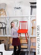 Купить «Salesgirl demonstrating wooden chairs in salon», фото № 33747951, снято 1 марта 2018 г. (c) Яков Филимонов / Фотобанк Лори