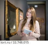 Купить «Woman with guide looking at pictures in museum», фото № 33748015, снято 18 ноября 2017 г. (c) Яков Филимонов / Фотобанк Лори