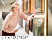 Купить «Woman with guide looking at pictures in museum», фото № 33748027, снято 18 ноября 2017 г. (c) Яков Филимонов / Фотобанк Лори
