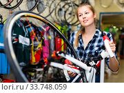 Купить «Portrait of woman who is standing with new bicycle indoors.», фото № 33748059, снято 13 сентября 2017 г. (c) Яков Филимонов / Фотобанк Лори