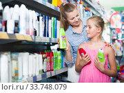 female with daughter holding conditioner for hair. Стоковое фото, фотограф Яков Филимонов / Фотобанк Лори